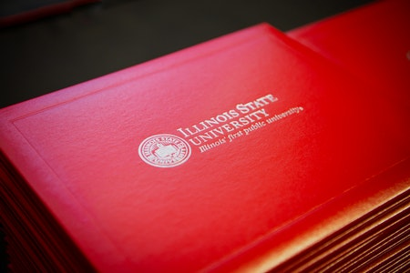 A neatly stacked pile of Illinois State University degrees.