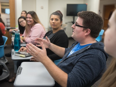 Graduate student talking to a group of students
