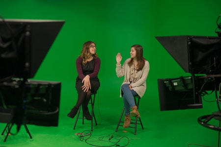 Two school of communication students on a green screen set recording for a news broadcast