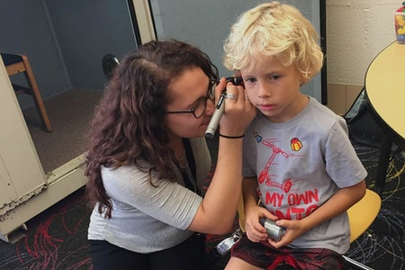 A student performing a screening hearing on a child patient.