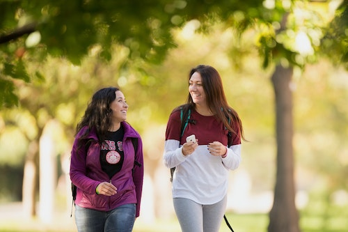 Two students walking together on the Quad