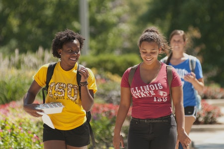 Two undergraduate students walking on the quad in the fall.